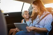 Smiling mother and happy little girl using digital tablet together in car. Mature woman showing vide poster