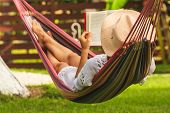Beautiful Woman Relaxing In Hammock. Beautiful Woman Reading Book In Hammock. Happy Beautiful Woman  poster