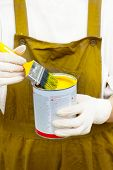 Woman In Boilersuite Handles Brush And Can With Yellow Paint