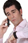 Man on the telephone checking watch