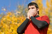 stock photo of snot  - Sick male athlete coughing and blowing her nose with a tissue beacuse autumnal illness - JPG