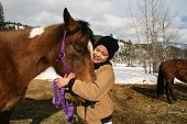 picture of reunited  - bundled up girl happily reunited with her horse - JPG