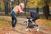 Young smiling mother looking at her child in a baby stroller
