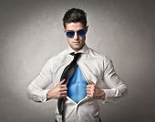 Muscular office worker with sunglasses opening his shirt like a superhero
