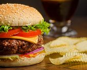 stock photo of beef-burger  - A deluxe cheeseburger with chips and cola - JPG