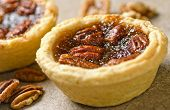 stock photo of pecan nut  - Mini pecan butter tarts with whole pecans against a plain rustic background - JPG