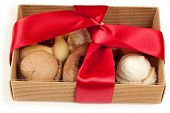Several kinds of cookies and cakes in open box of corrugated cardboard, tied with red ribbon