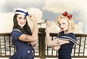 stock photo of pinup girl  - Artistic portrait of two sexy sailor pin up girls with anchor tattoos flexing muscles on a vintage pier promenade when competing in strength and conditioning exercises - JPG
