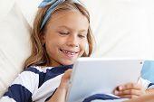 Kind spielen auf Tablet-pc auf dem Sofa zu Hause
