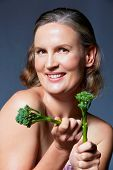 beautiful fourty year old woman with natural makeup and healthy skin texture on blue gray studio background holding a broccoli in her hands