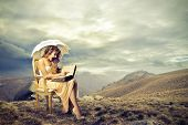 elegant girl with umbrella sitting on antique chair in the mountain reading a big book