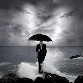 pic of under sea  - Business man under an umbrella standing on a rock in the sea with lightning sky business concept - JPG