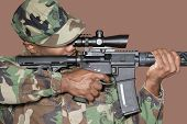 foto of corps  - Male US Marine Corps soldier aiming M4 assault rifle over brown background - JPG