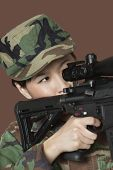 stock photo of m4  - Young female US Marine Corps soldier aiming M4 assault rifle over brown background - JPG