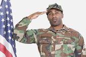 stock photo of corps  - Portrait of US Marine Corps soldier saluting American flag over gray background - JPG
