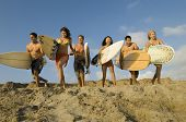 Group of multiethnic friends with surfboards running on sandy beach