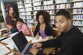 Group of multiethnic college students studying together in library