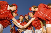 stock photo of softball  - Happy female softball players stacking hands against clear blue sky - JPG