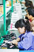 female chinese worker woman assembling production at line conveyor in china factory manufacturing