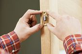 Two worker hands of carpenter at lock installation into wood door
