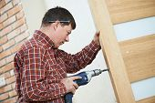 foto of carpenter  - carpenter at lock installation with electric drill into interior wood door - JPG