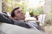 Side view of a young businessman with earphones relaxing at home