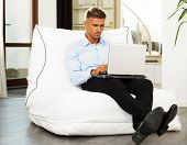Goodlooking mature man relaxing at home in armchair with laptop