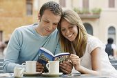 Smiling young couple at outdoor cafe looking at guidebook of Rome