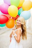 summer holidays, celebration and lifestyle concept - beautiful woman with colorful balloons in the city