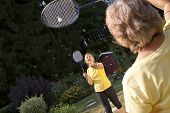 image of badminton player  - Two women playing badminton in the garden - JPG