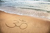 picture of om  - Om symbol on the sand at the beach near the ocean - JPG
