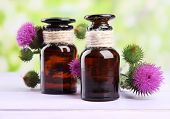 Medicine bottles with thistle flowers on nature background