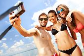 image of suntanning  - Portrait of happy friends taking photo of themselves on the beach - JPG