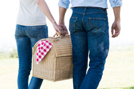 picture of nic  - Young Couple Walking Holding Picnic Basket Together - JPG