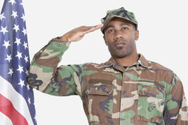 stock photo of united states marine corps  - Portrait of US Marine Corps soldier saluting American flag over gray background - JPG