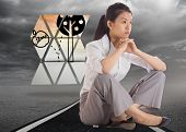 Thinking businesswoman sitting with hands together against street under stormy sky