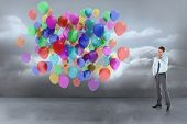 Thoughtful businessman with hand on chin against many colourful balloons in cloudy room