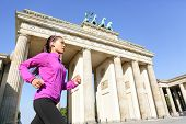Running woman in Berlin, Germany by Brandenburg Gate jogging living healthy lifestyle. Female runner