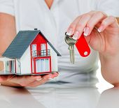 a broker for real estate with a house and a key. rent and house sale by real estate agents.
