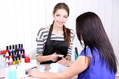 Beautiful girl manicurist doing manicure for woman in beauty salon