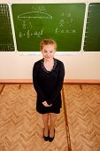 Exemplary student standing near the blackboard at a classroom and smiling. Education.