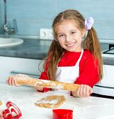 little girl unrolls dough for cookies for the Valentine's Day