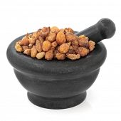 Pinellia tuber chinese herbal medicine in a black stone mortar with pestle over white background. Ban xia.