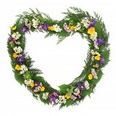 Wild flower heart shaped wreath over white background.