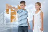 Young boy showing something to his sister against room with holographic cloud