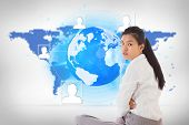Businesswoman sitting cross legged frowning against blue world map on white background