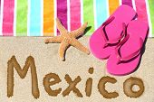 Mexico beach travel concept. MEXICO written in sand with water next to beach towel and summer sandal
