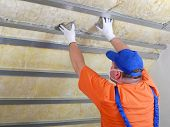foto of attic  - Construction worker thermally insulating house attic with mineral wool - JPG