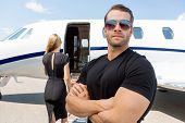 stock photo of jet  - Confident bodyguard wearing sunglasses while standing against woman and private jet - JPG