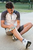 foto of knee  - Young Male Athlete Sitting On Ground And Taking Ice For Knee Pain - JPG